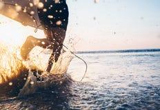Persona que practica surf del hombre funcionada con en el océano con la tabla hawaiana Spla del agua de la imagen del primer Imagen de archivo