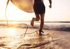 Persona que practica surf del hombre funcionada con en el océano con la tabla hawaiana Vacaciones activas, salud Imagen de archivo