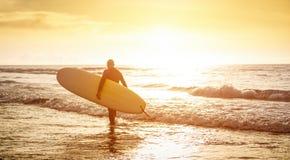 Persona que practica surf del individuo que camina con la tabla hawaiana en la puesta del sol en Tenerife - practique surf el con foto de archivo libre de regalías