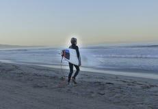 Persona que practica surf del muchacho que camina en el océano Fotos de archivo libres de regalías
