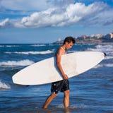 Persona que practica surf del muchacho que sostiene la tabla hawaiana caming hacia fuera de las ondas Imágenes de archivo libres de regalías