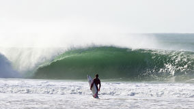 Persona que practica surf delante de una onda grande Fotografía de archivo