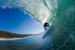 Persona que practica surf dentro de la onda hueco   Imagen de archivo libre de regalías