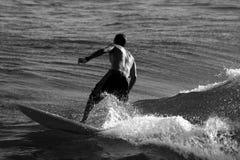 Persona que practica surf en blanco y negro Foto de archivo