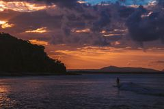 Persona que practica surf en el agua tranquila en luz de la puesta del sol imágenes de archivo libres de regalías