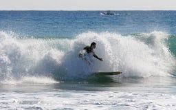Persona que practica surf en el final de su corrida Foto de archivo
