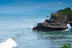 Persona que practica surf en el templo de Pura Tanah Lot en Bali Imagenes de archivo
