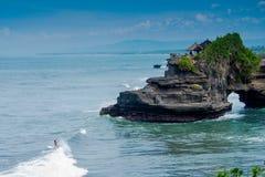Persona que practica surf en el templo en Bali, Indonesia de Pura Tanah Lot Fotos de archivo