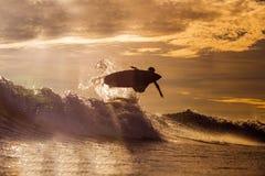 Persona que practica surf en el tiempo de la puesta del sol fotografía de archivo