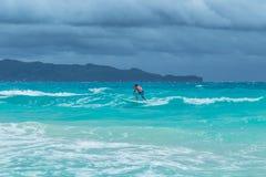 Persona que practica surf en la ola oceánica azul de la turquesa en Siargao, Filipinas fotos de archivo