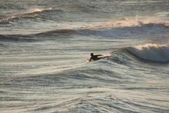 Persona que practica surf en la oscuridad Fotos de archivo