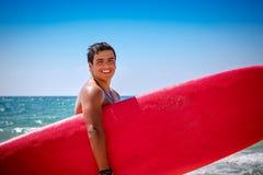 Persona que practica surf en la playa Fotos de archivo