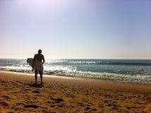 Persona que practica surf en la playa Imagen de archivo libre de regalías