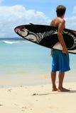 Persona que practica surf en la playa con la tabla hawaiana cobarde de los arty Foto de archivo libre de regalías