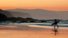 Persona que practica surf en la playa en la puesta del sol Imagen de archivo libre de regalías