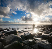 Persona que practica surf en la playa rocosa en la luz llamativa Fotografía de archivo