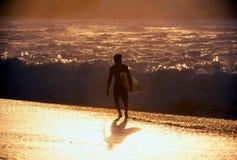 Persona que practica surf en la puesta del sol imagen de archivo