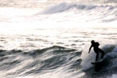 Persona que practica surf en la puesta del sol Fotografía de archivo libre de regalías