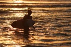 Persona que practica surf en la puesta del sol Foto de archivo libre de regalías