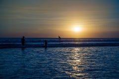 Persona que practica surf en la puesta del sol Foto de archivo