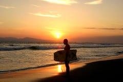 Persona que practica surf en la puesta del sol Imágenes de archivo libres de regalías