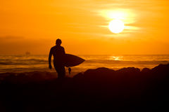 Persona que practica surf en la puesta del sol Fotos de archivo