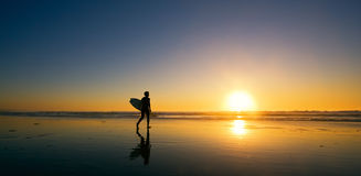 Persona que practica surf en la puesta del sol Imagen de archivo libre de regalías