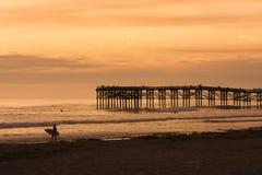 Persona que practica surf en la puesta del sol Fotografía de archivo