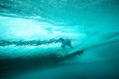 Persona que practica surf en la visión subacuática de la onda tropical Foto de archivo libre de regalías