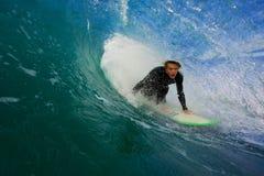 Persona que practica surf en onda azul en tubo Foto de archivo libre de regalías