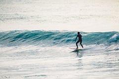 Persona que practica surf en paseo del wetsuit en onda azul Invierno que practica surf en el océano Imágenes de archivo libres de regalías