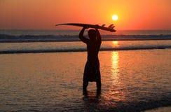 Persona que practica surf en puesta del sol Imagenes de archivo