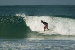 Persona que practica surf en una onda Foto de archivo libre de regalías