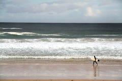 Persona que practica surf en una playa Imagenes de archivo