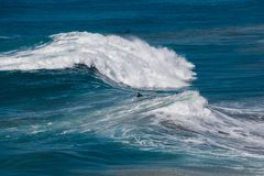 Persona que practica surf entre las ondas en la tabla fotografía de archivo