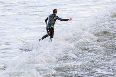 Persona que practica surf que equilibra en la tabla hawaiana en el medio de las ondas del mar imágenes de archivo libres de regalías