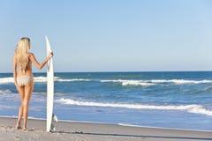 Persona que practica surf hermosa de la mujer en playa de la tabla hawaiana del bikiní Imagen de archivo libre de regalías