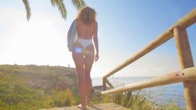 Persona que practica surf hermosa de la mujer joven que camina abajo de la playa en la puesta del sol almacen de metraje de vídeo