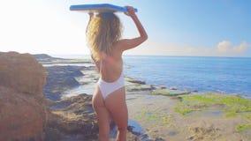 Persona que practica surf hermosa de la mujer joven que camina abajo de la playa en la puesta del sol almacen de video