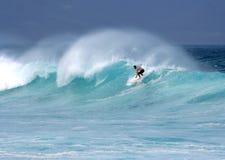 Persona que practica surf joven en aerosol ventoso de la onda Imagenes de archivo