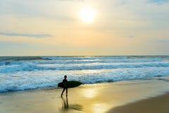 Persona que practica surf joven en la playa Imagenes de archivo