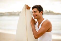 Persona que practica surf joven que se coloca con su tabla hawaiana Fotografía de archivo