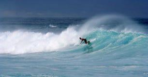 Persona que practica surf joven y aerosol ventoso de la onda Fotografía de archivo