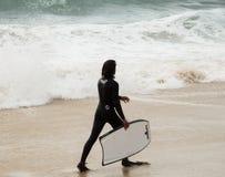 Persona que practica surf joven y las olas oceánicas fotos de archivo