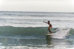 Persona que practica surf local que monta las ondas en Sri Lanka Imagen de archivo libre de regalías