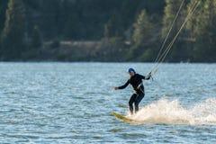 Persona que practica surf mayor de la cometa en el río fotografía de archivo