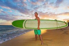 Persona que practica surf optimista en la puesta del sol foto de archivo