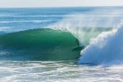 Persona que practica surf que practica surf paseo hueco del tubo de la onda Imagen de archivo libre de regalías