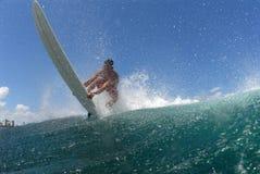 Persona que practica surf que baja de una onda imagenes de archivo