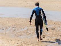 Persona que practica surf que camina en el warter en el sol en la playa Imagen de archivo